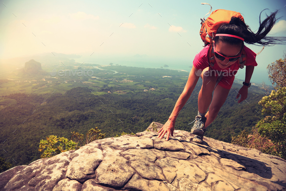Successful woman climbing up on mountain top cliff edge - Stock Photo - Images