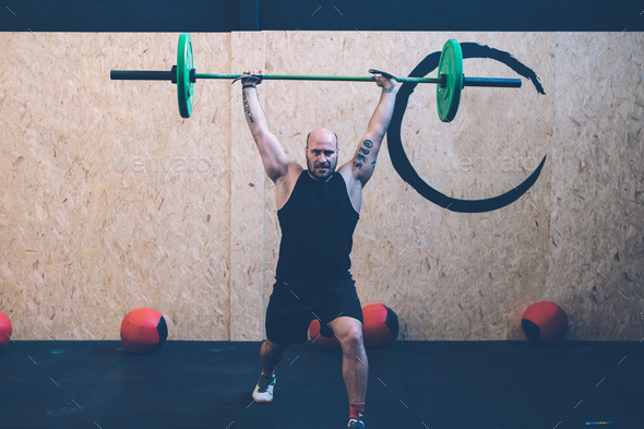 Man doing jerks with barbell - Stock Photo - Images