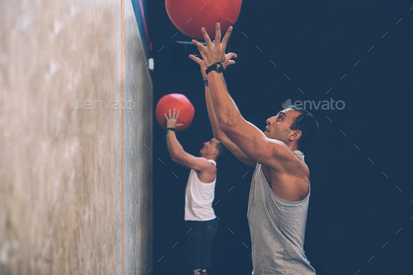 Sporty men doing wall ball exercise  - Stock Photo - Images
