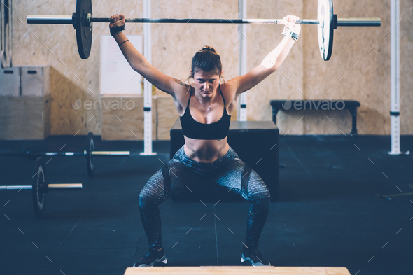 Girl doing barbell snatch - Stock Photo - Images