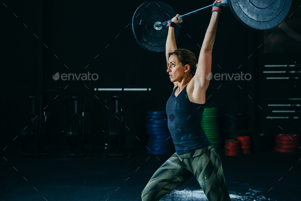 Woman does jerk with barbell - Stock Photo - Images