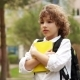 A Cute, Curly Schoolboy Is Standing with a Knapsack Behind His Back and a Book in His Hands - VideoHive Item for Sale