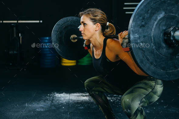 Girl doing back squat - Stock Photo - Images