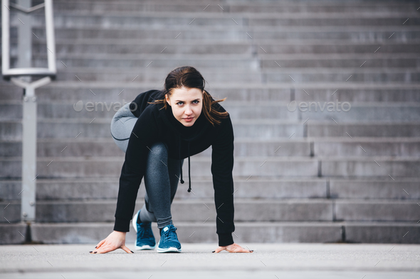 Woman in sports clothes ready to run. - Stock Photo - Images