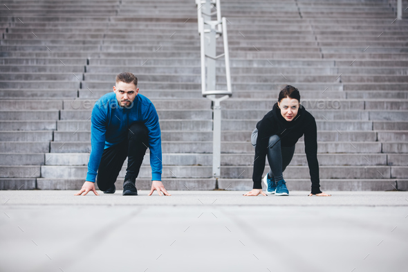 Young athletic couple in a steady position crouching. - Stock Photo - Images
