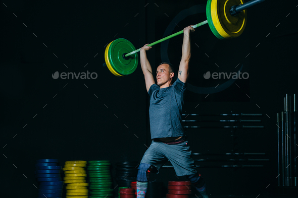 Man doing jerk with barbell - Stock Photo - Images