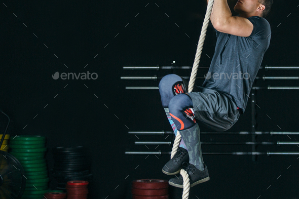 Man doing rope climb exercise - Stock Photo - Images