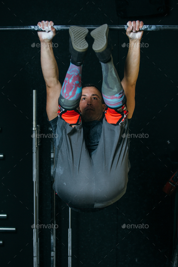 Man doing toes to bar exercise - Stock Photo - Images