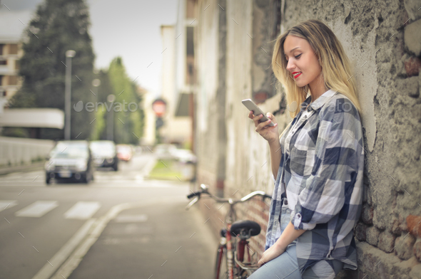 Girl with a smartphone outdoor - Stock Photo - Images