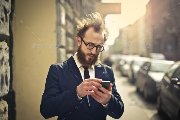 Man looking at a smartphone outdoor - Stock Photo - Images