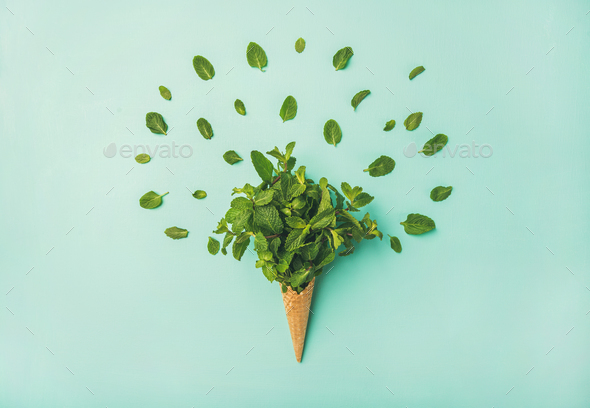 Waffle cone with fresh mint over blue background, top view - Stock Photo - Images