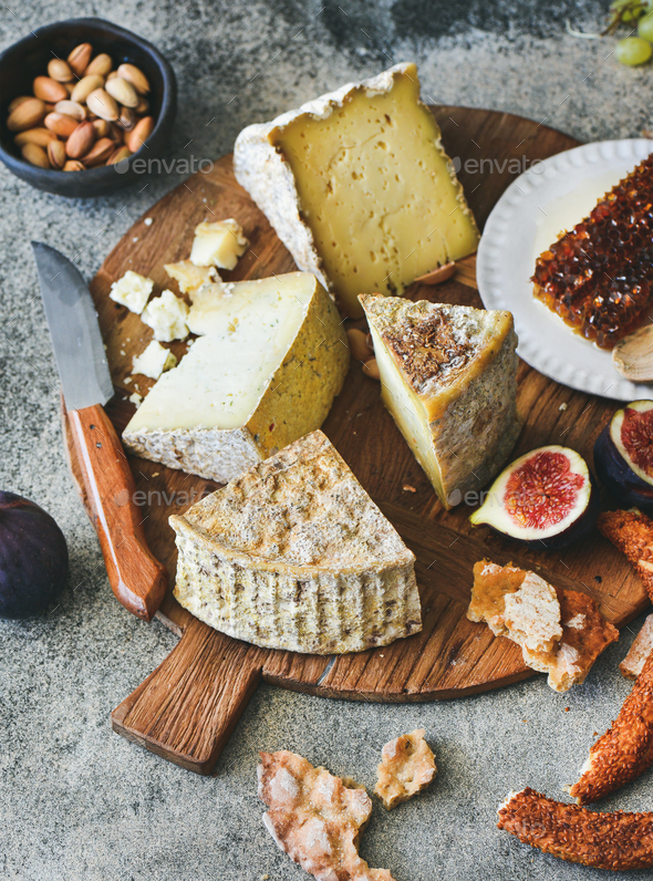 Cheese assortment, figs, honey, fresh bread and nuts - Stock Photo - Images