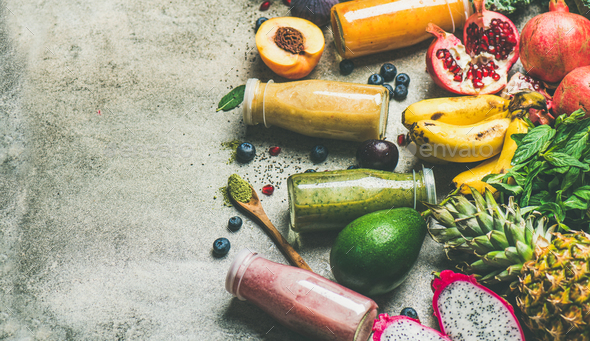 Colorful smoothies in bottles with fresh fruit, copy space - Stock Photo - Images
