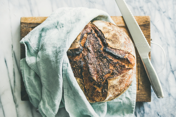Freshly baked sourdough bread on chopping board - Stock Photo - Images
