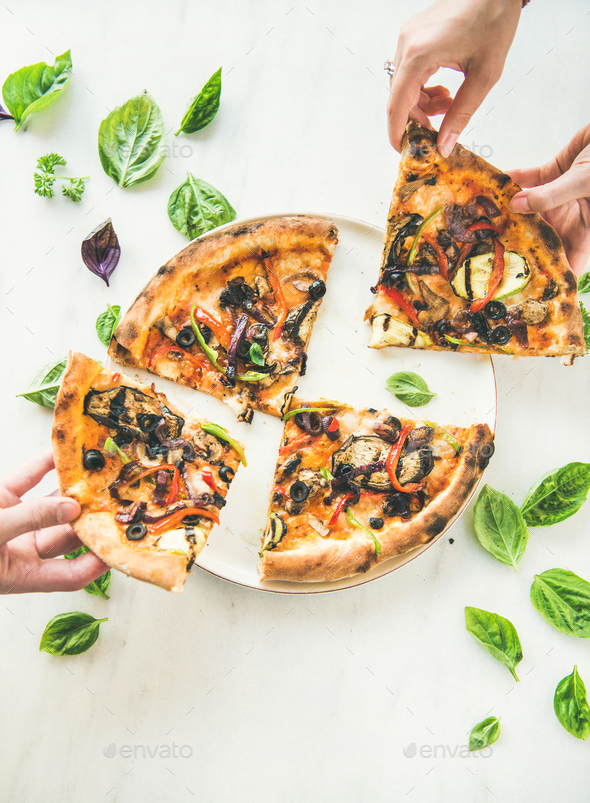 People's hands taking Freshly baked vegetarian pizza over marble background - Stock Photo - Images