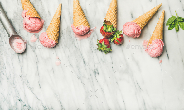 Flat-lay of homemade yogurt strawberry ice cream in waffle cones - Stock Photo - Images