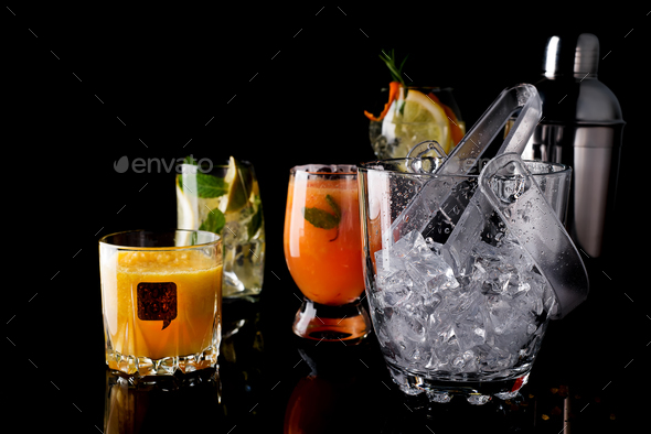 Glass ice bucket and Different cocktails in glass with Bar accessories isolated on black - Stock Photo - Images