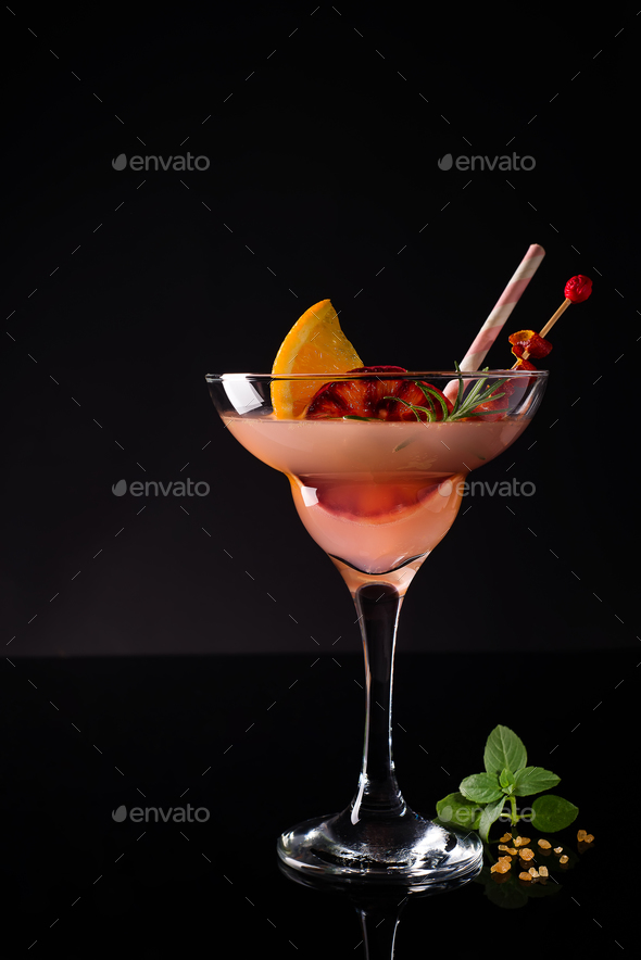 Freshly made Margarita cocktails in glasses with mint and orange in black. - Stock Photo - Images
