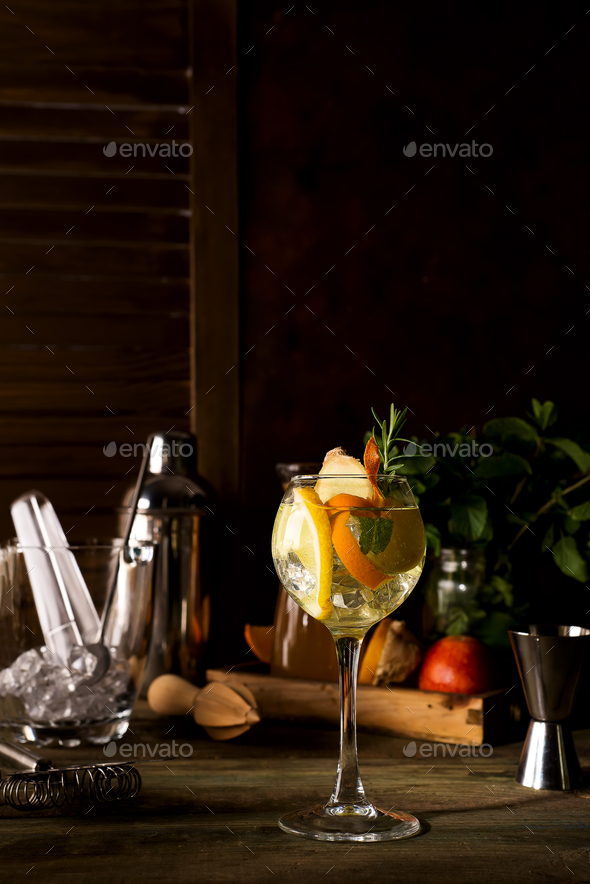 Cocktail with rosemary, lemon and orange on dark wooden backgorund - Stock Photo - Images