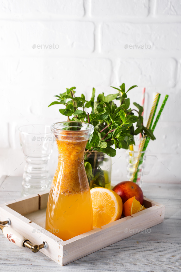 Orange lemonade in the decanter on a wooden tray with ftuits and mint - Stock Photo - Images