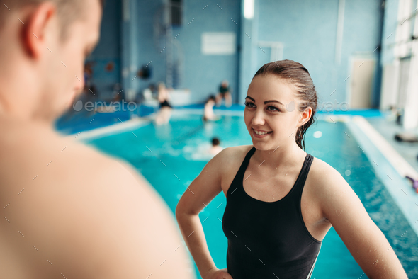 Swimmers talking on training against swimming pool - Stock Photo - Images