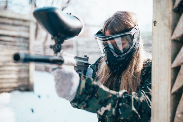 Female paintball player with marker gun in hands - Stock Photo - Images