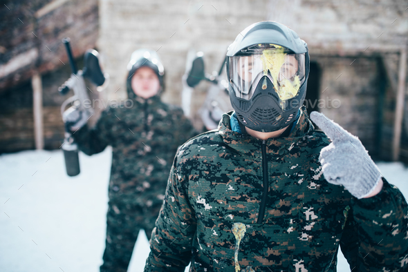 Paintball player points finger at splattered mask - Stock Photo - Images
