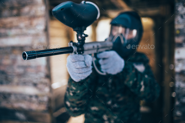 Paintball player with marker gun, front view - Stock Photo - Images