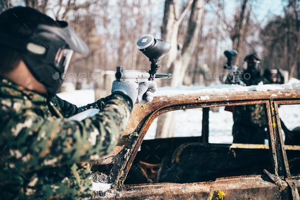 Paintball players shoots because of burned car - Stock Photo - Images