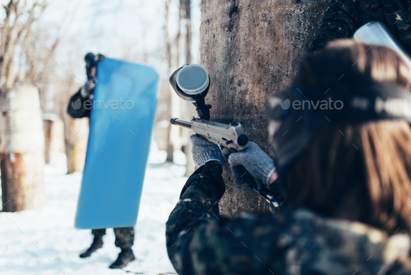 Paintball player shooting at enemy with the shield - Stock Photo - Images