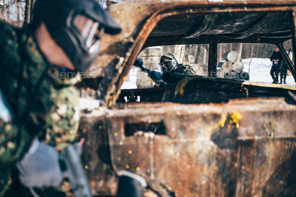 Paintball battle, players fight around burned car - Stock Photo - Images
