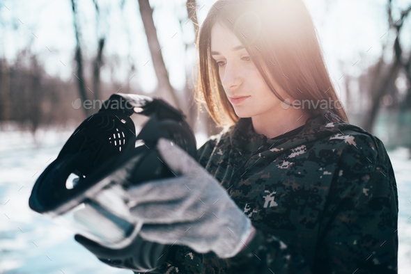 Female paintball player puts on protection mask - Stock Photo - Images