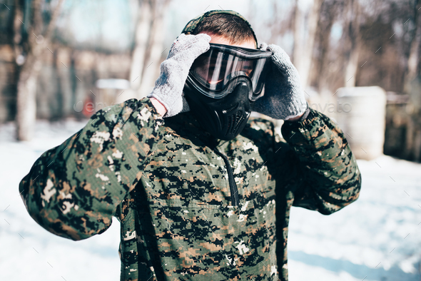 Male paintball player puts on protection mask - Stock Photo - Images
