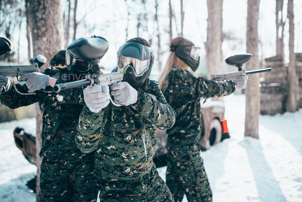 Paintball players in uniform and masks poses - Stock Photo - Images