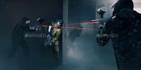 Paintball team in battle, guns with a laser sight - Stock Photo - Images
