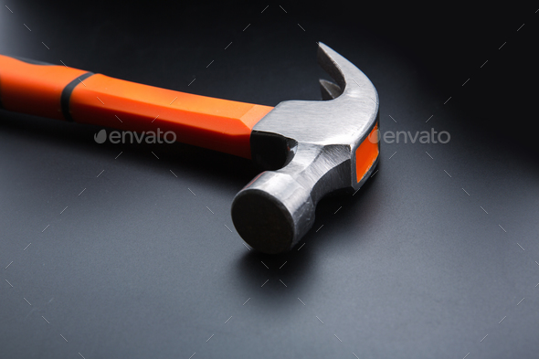 Orange hammer on dark matt background, closeup - Stock Photo - Images