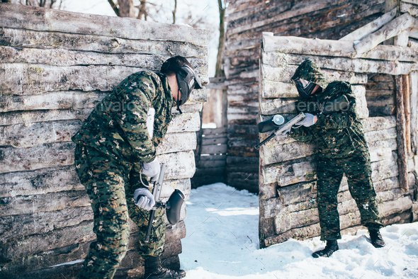 Paintball battle, paintballing in winter forest - Stock Photo - Images
