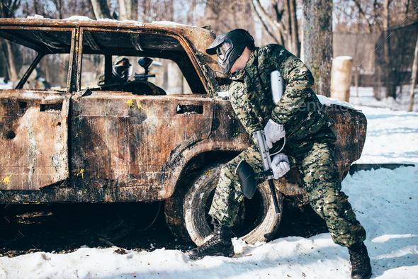 Paintball battle, burned car in winter forest - Stock Photo - Images
