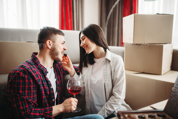 Couple drink wine, moving to new house celebration - Stock Photo - Images