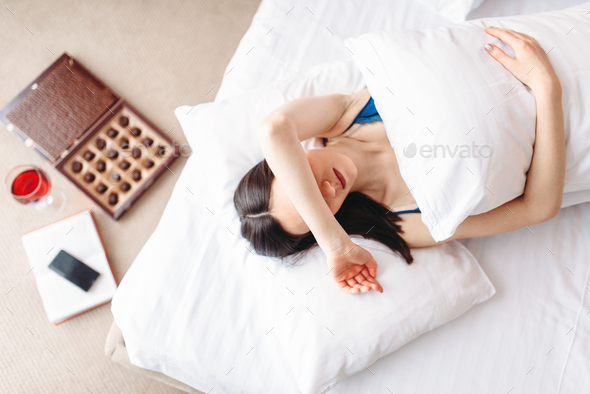 Woman lies under the blanket, top view, depression - Stock Photo - Images