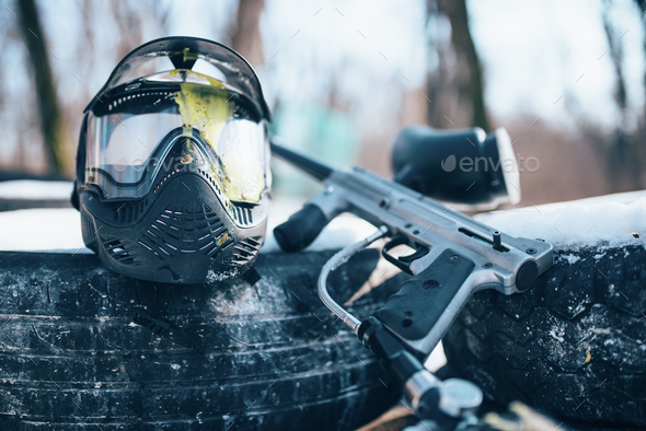 Splattered paintball mask and marker gun - Stock Photo - Images