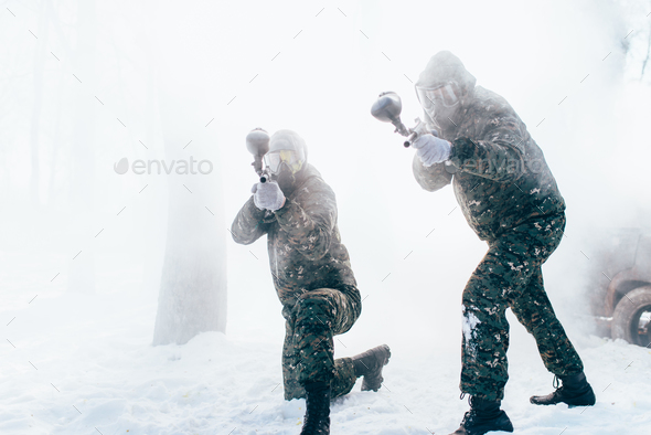 Two paintball players shooting at the enemy - Stock Photo - Images