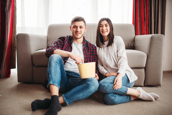 Couple sitting on floor and watch tv with popcorn - Stock Photo - Images