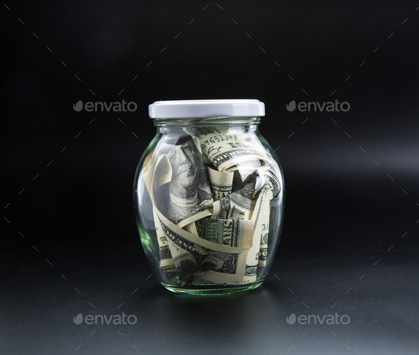 Money saving concept, glass jar full of dollars - Stock Photo - Images