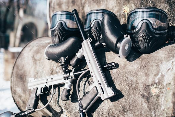 Paintball masks with glasses and marker guns - Stock Photo - Images