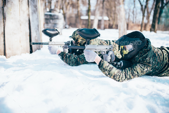 Two paintball players lies on the snow - Stock Photo - Images