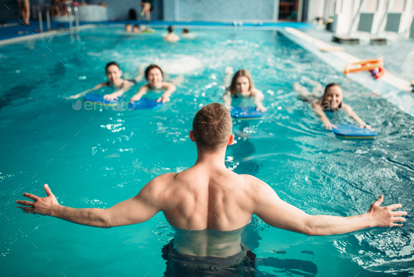 Trainer works with female group in swimming pool - Stock Photo - Images