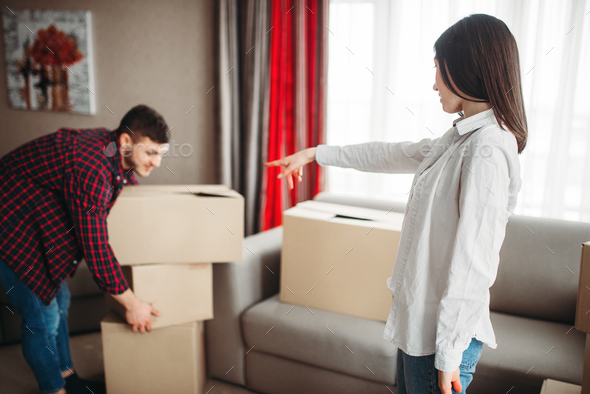 Happy couple arrange cardboard boxes on a room - Stock Photo - Images