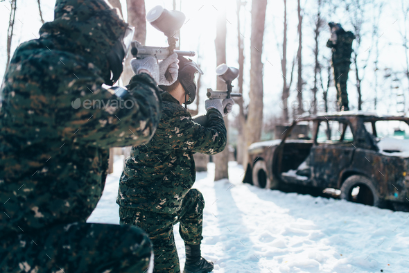 Paintball players shooting at enemy, winter battle - Stock Photo - Images