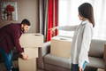 Happy couple arrange cardboard boxes on a room - PhotoDune Item for Sale